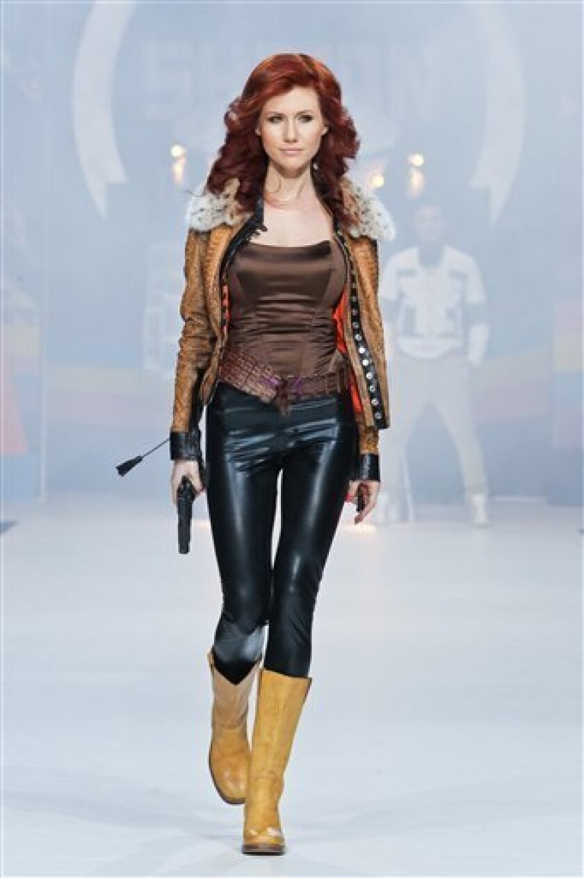In this photo taken on Sunday, April 3, 2011, Anna Chapman, who was deported from the U.S. on charges of espionage, displays a creation by Russian designers Shiyan & Rudkovskaya during a Fashion Week in Moscow, Russia. A year and a half after the biggest spy swap since the Cold War, its Russian pro