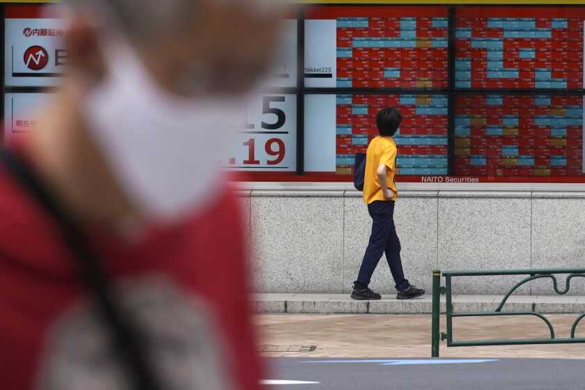 A man looks at an electronic stock board showing Japan's Nikkei 225 index at a securities firm in Tokyo Friday, July 3, 2020. Markets advanced in Asia on Friday following a Wall Street rally driven by strong jobs data. (AP Photo/Eugene Hoshiko)