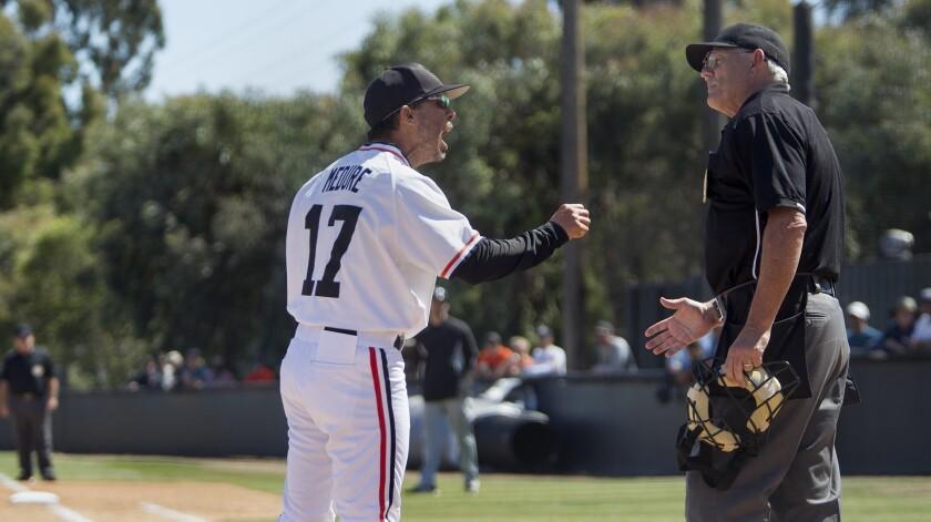 Huntington Beach High coach Benji Medure disputes a call during the first inning against El Dorado i