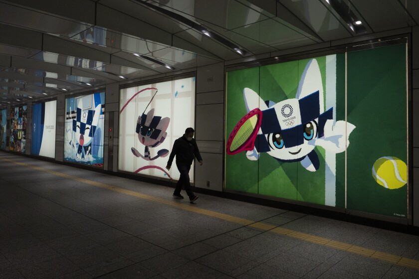 An individual walks past promotional images of the 2020 Olympics in Tokyo on Tuesday, the day the IOC announced the Games would be postponed until 2021.