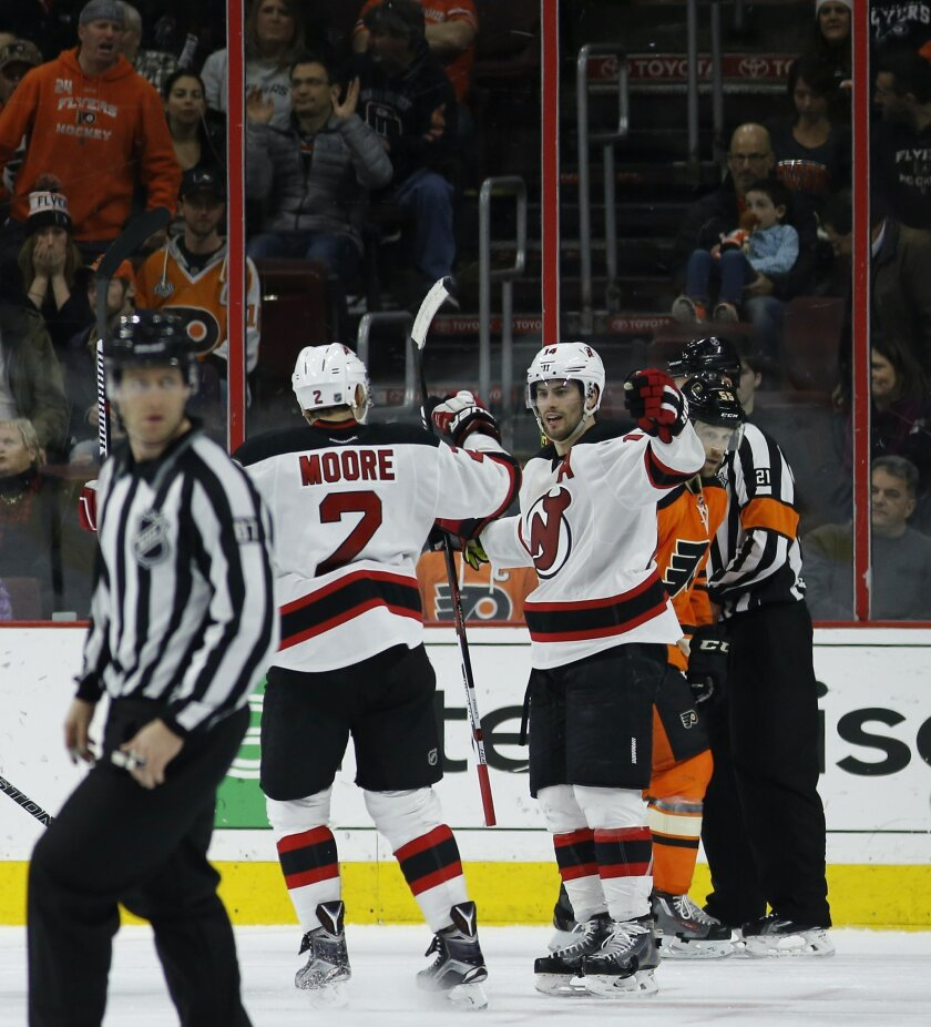 New Jersey Devils' Adam Henrique (14) celebrates with John Moore (2) past Philadelphia Flyers' Nick Schultz (55) after Henrique's game-winning goal during overtime of an NHL hockey game, Saturday, Feb. 13, 2016, in Philadelphia. New Jersey won 2-1. (AP Photo/Matt Slocum)