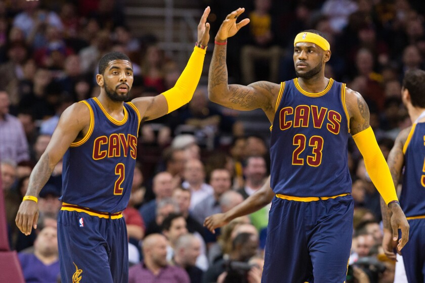 Cavaliers point guard Kyrie Irving (2) and forward LeBron James (23) share a high five
