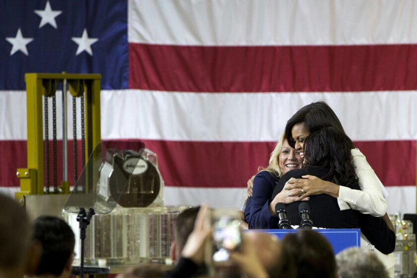 First lady Michelle Obama hugs April Arnzen, vice president of human resources at Micron Technology, left, and Tamika Carroll, a buyer at Micron Technology before speaking at Micron Technology, Inc., a semiconductor manufacturer, Thursday, April 23, 2015, in Manassas, Va., to announce new commitments to train and hire veterans, and military spouses. (AP Photo/Jacquelyn Martin)