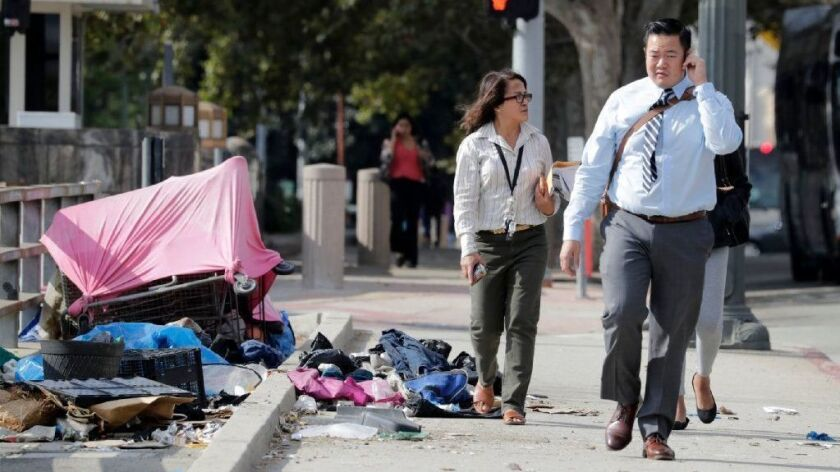 Pedestrians walk by trash spilling out of a tent on Spring Street in Los Angeles.