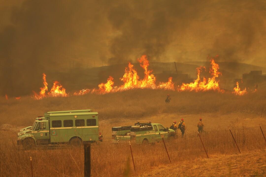 Firefighters watch grass burn