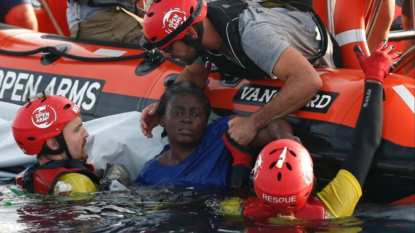Members of Proactiva Open Arms, a Spanish aid group, rescue a woman on July 17, 2018, about 80 nautical miles from the Libyan coast, in the Mediterranean Sea.