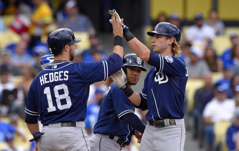 San Diego Padres' Travis Jankowski, right, is congratulated by Austin Hedges, left, and Alexi Amarista after hitting a three-run home run during the seventh inning of a baseball game against the Los Angeles Dodgers, Sunday, Oct. 4, 2015, in Los Angeles. (AP Photo/Mark J. Terrill)