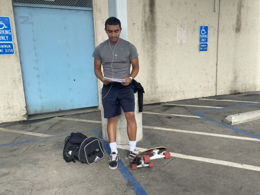 Daniel Najar stands with one foot on his tipped up skateboard.