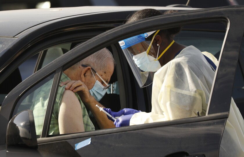 Staff and volunteers distribute the COVID-19 vaccine to people as they remain in their vehicles at the Forum in Inglewood.