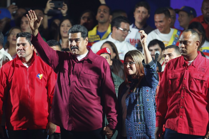 Venezuela's President Nicolas Maduro and his wife Cilia Flores wave to supporters after the National Electoral Council announced that with almost 93 percent of polling stations reporting, Maduro won nearly 68 percent of the votes in Sunday's election, beating his nearest challenger Henri Falcon by almost 40 points, in Caracas, Venezuela, Sunday, May 20, 2018.