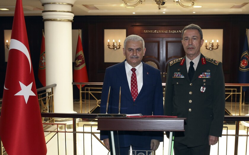 Turkish Prime Minister Binali Yildirim, left, flanked by Chief of Staff Gen. Hulusi Akar, speaks to the press in Ankara on June 2, 2016, about the decision by Germany's parliament to recognize the Armenian genocide.