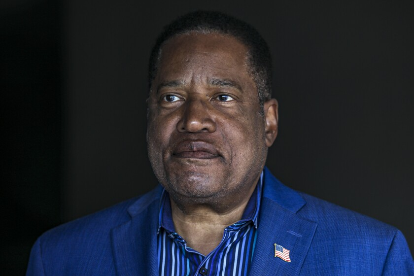 A closeup of Larry Elder in an open collar shirt and suit jacket.