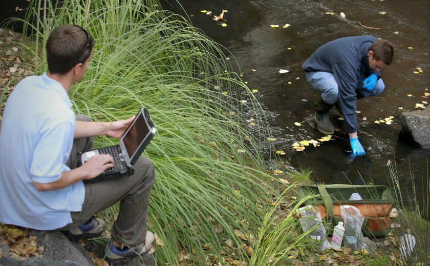 William Svec, a biologist with the city of San Diego Transportation and Stormwater Department, left, records information while intern Sean Mulderig, right, takes water samples from a storm drain system channeled creek along Murphy Canyon Road. / photo by Howard Lipin * U-T