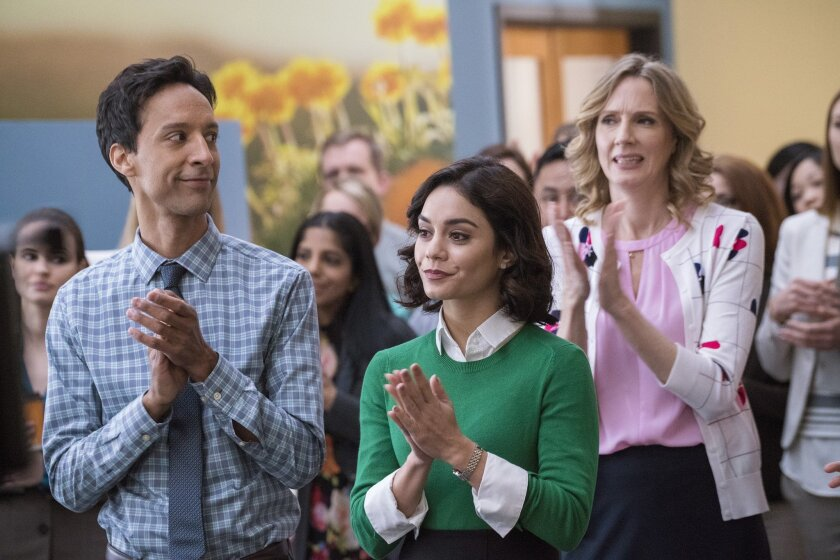 """This photo provided by NBC shows, Danny Pudi, from left, as Teddy, Vanessa Hudgens as Emily, and Christina Kirk as Jackie in the NBC television pilot for """"Powerless.""""  A comedy series starring Hudgens and set in the DC Comics world is coming to NBC. The network said Wednesday, May 11, 2016, it's or"""
