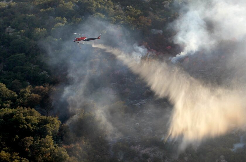 At 6:00 p.m. a helicopter makes a fire retardant drop on a hot spot of a 45 acre brush fire on the steep west side of Pala Temecula Road near the Riverside County line. The fire began at a house fire at 38850 Pala Temecula Road. Residents of homes nearby have been evacuated to Great Oak High School