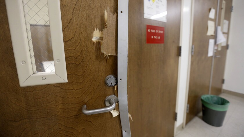 Smashed doors can be seen on the fourth floor of the UCLA engineering building where Wednesday's murder-suicide took place.