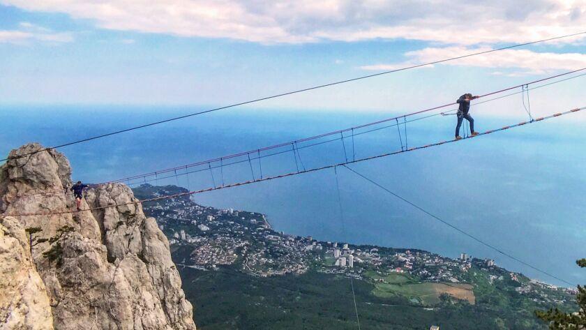 CRIMEA, RUSSIA - A tourist walks the last few feet of a cable bridge atop Ai-Petr, at more than 4,00