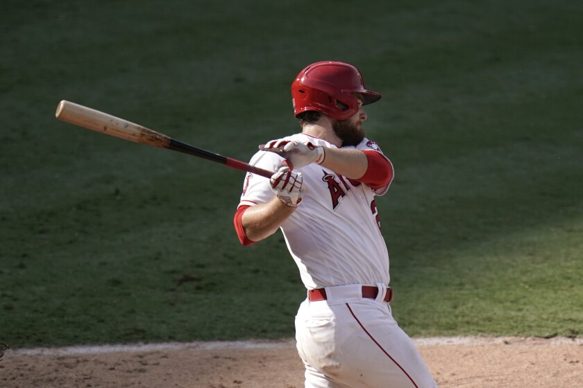 Los Angeles Angels' Jared Walsh follows through after hitting an RBI single during the eighth inning.