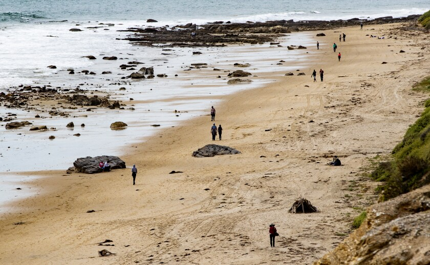 People walk along the shore at Crystal Cove State Beach.
