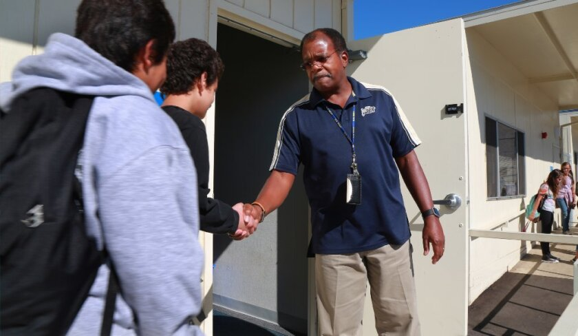 San Marcos, CA. USA November 3, 2016 | Eighth grade social science teacher Elliott Powell, a former U.S. Navy captain and White House Situation Room Director makes a point of greeting each student with a handshake as they enter, each day.