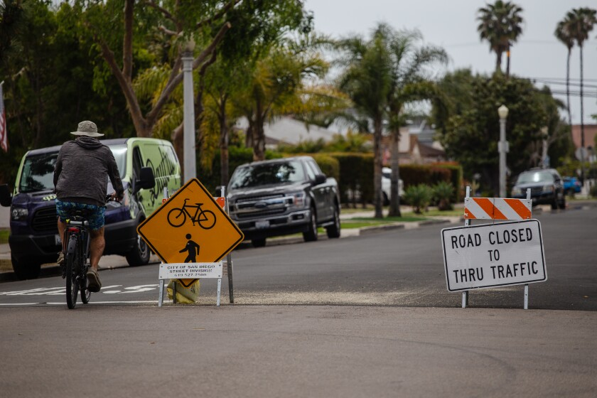A cyclist rides past road traffic signs on Diamond Street in Pacific Beach on Wednesday, May 5, 2021.