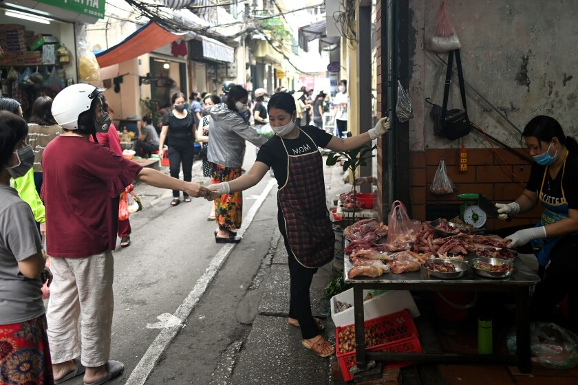 Shoppers practice social distancing at a market in Hanoi, Vietnam, on Sunday.