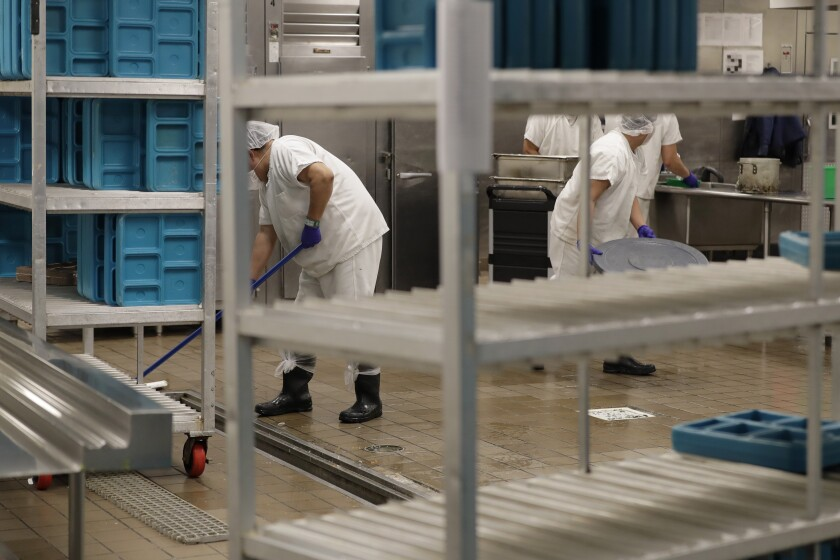 In this photo taken Sept. 10, 2019, workers are shown in the kitchen of the U.S. Immigration and Customs Enforcement (ICE) detention facility in Tacoma, Wash. during a media tour. On Tuesday, Sept. 24, 2019, U.S. District Judge Robert Bryan notified attorneys for Washington state and the GEO Group -- which operates the detention center -- that he plans to dismiss a case in which Washington state was pursuing a claim that immigration detainees must be paid minimum wage for work they perform in custody. (AP Photo/Ted S. Warren)