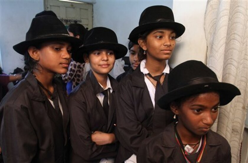 Indian girls wait for their turn to be made up to look like Charlie Chaplin to participate in the annual parade to celebrate his birthday in Adipur, Gujarat state, India, Tuesday, April 16, 2013. Canes in hand and bowler hats firmly in place, dozens of Charlie Chaplin impersonators tramped through