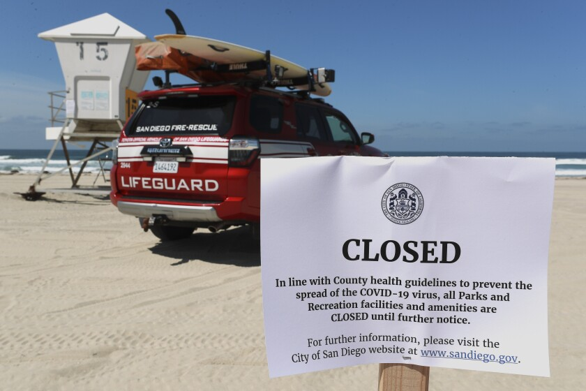 Signs are posted on March 28, 2020, at Mission Beach in San Diego, which is closed because of the coronavirus outbreak.
