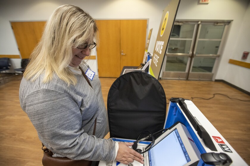 Catherine Miller casts a mock vote on a voting machine during a presentation Wednesday at the Costa Mesa Senior Center about changes to voting systems that begin with this year's California primary election.