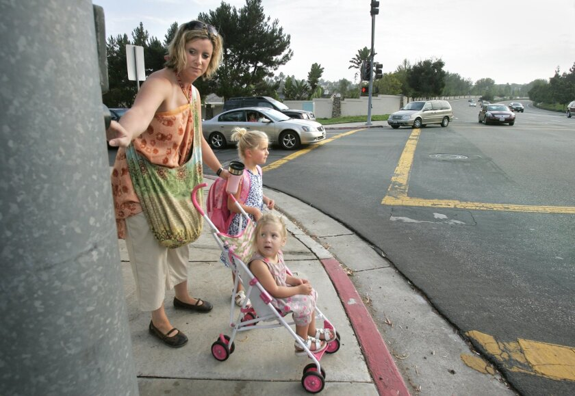Rachel Nieting walked her daughter Kaylee to kindergarten at Shoal Creek Elementary School. Since the school opened in 1998, parents have talked about the need for a safer crossing. (Charlie Neuman / Union-Tribune)