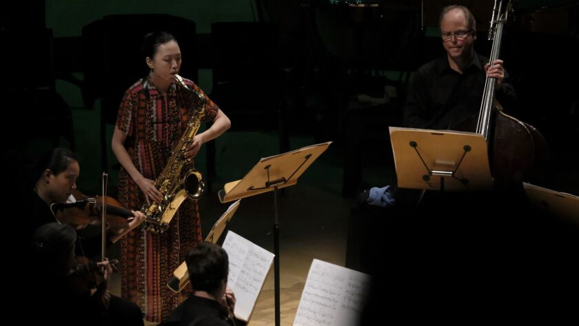 "Saxophonist Hitomi Oba solos in her new piece, ""Aina,"" with the Los Angeles Philharmonic New Music Group as part of a Green Umbrella program at Walt Disney Concert Hall Tuesday night."