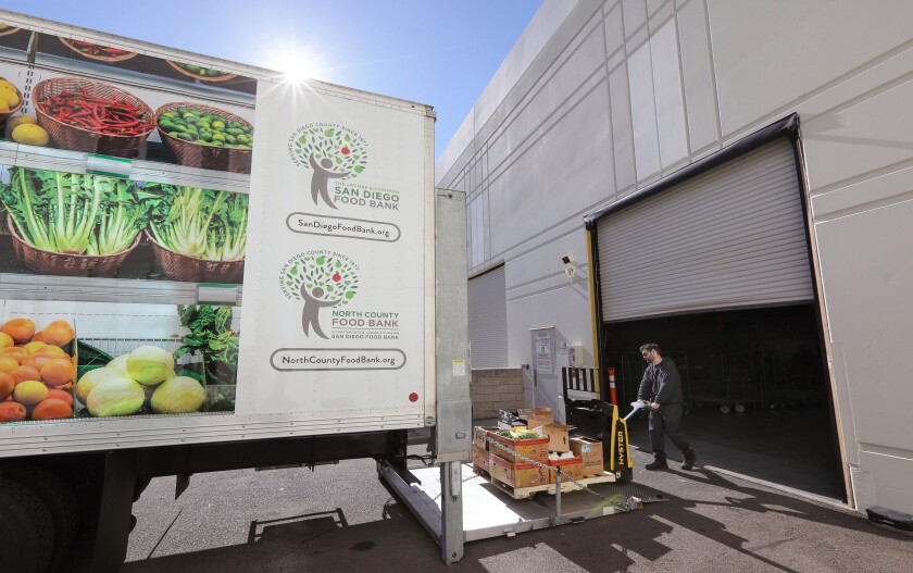 Jaime Borges, a driver for the San Diego Food Bank, unloads donated food at the warehouse loading dock of the San Diego Food Bank's new North County location in November.