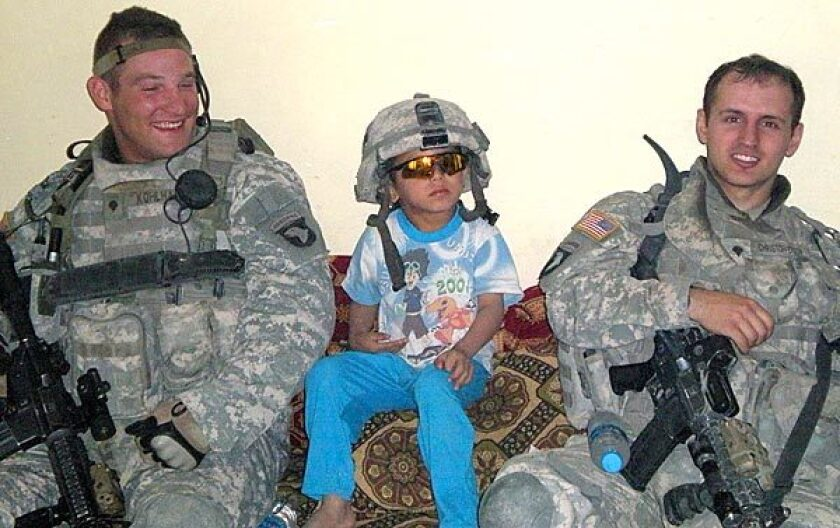 """Army Spc. Adam Kohlhaas, left, and Spc. Steven Christofferson with an Iraqi child the day before their vehicle was hit by a roadside bomb. Their deaths sent 1st Lt. Michael Behenna on """"a mission to find out who was responsible,"""" according to one soldier."""