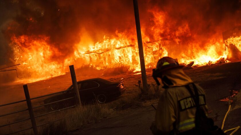 A barn is engulfed in flames as the River fire, part of the Mendocino Complex, spreads with the wind near Hendricks Road in Lake County, Calif., on July 31.