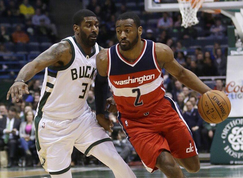 Washington Wizards' John Wall (2) drives against Milwaukee Bucks' O.J. Mayo (3) during an NBA basketball game Thursday, Feb. 11, 2016, in Milwaukee. (AP Photo/Aaron Gash)
