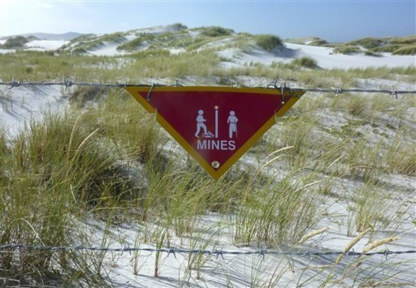 In this Sunday March 4, 2012 photo, a sign warns of land mines just outside Stanley, Falkland Islands. Many scars remain from Argentina's occupation of the islands, both physical and those harder to see at first. The beautiful white-sand beach where Argentine troops came ashore on April 2, 1982 rem