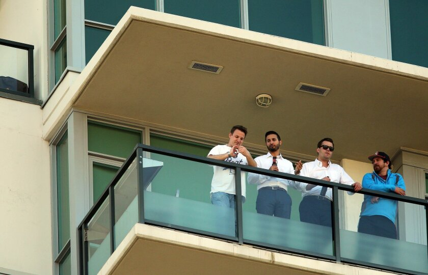 Baseball fans watch a San Diego Padres game last week from a downtown apartment building.