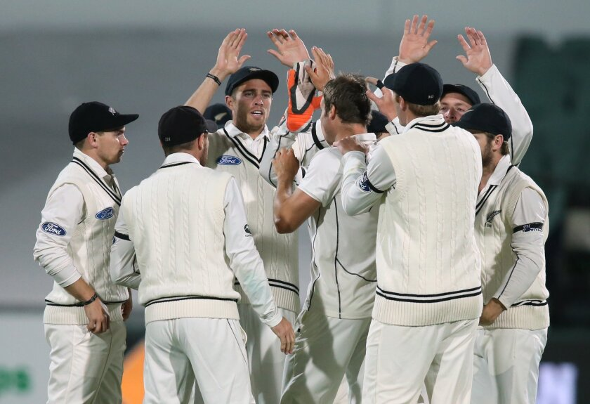 """New Zealand players celebrate after dismissing Australia's Joe Burns during their cricket test in Adelaide, Friday, Nov. 27, 2015. This match is the sport's first ever day-night test and the use of the """"experimental"""" pink leather ball replacing the standard-issue red for the first time in a format that dates back to the 1870s. (AP Photo/Rick Rycroft)"""