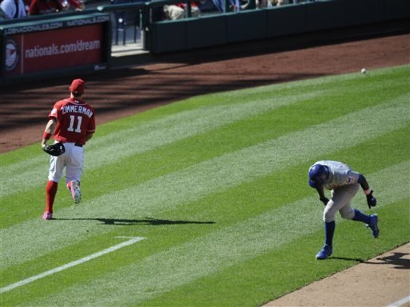 Chicago Cubs' Alfonso Soriano, right, heads for home after he stole third as Washington Nationals third baseman Ryan Zimmerman, left, looks for ball thrown by catcher Kurt Suzuki during the ninth inning of a baseball game, Sunday, May 12, 2013, in Washington. Soriano proceeded to score and Suzuki was charged with a throwing error on the play. The Cubs won 2-1. (AP Photo/Nick Wass)