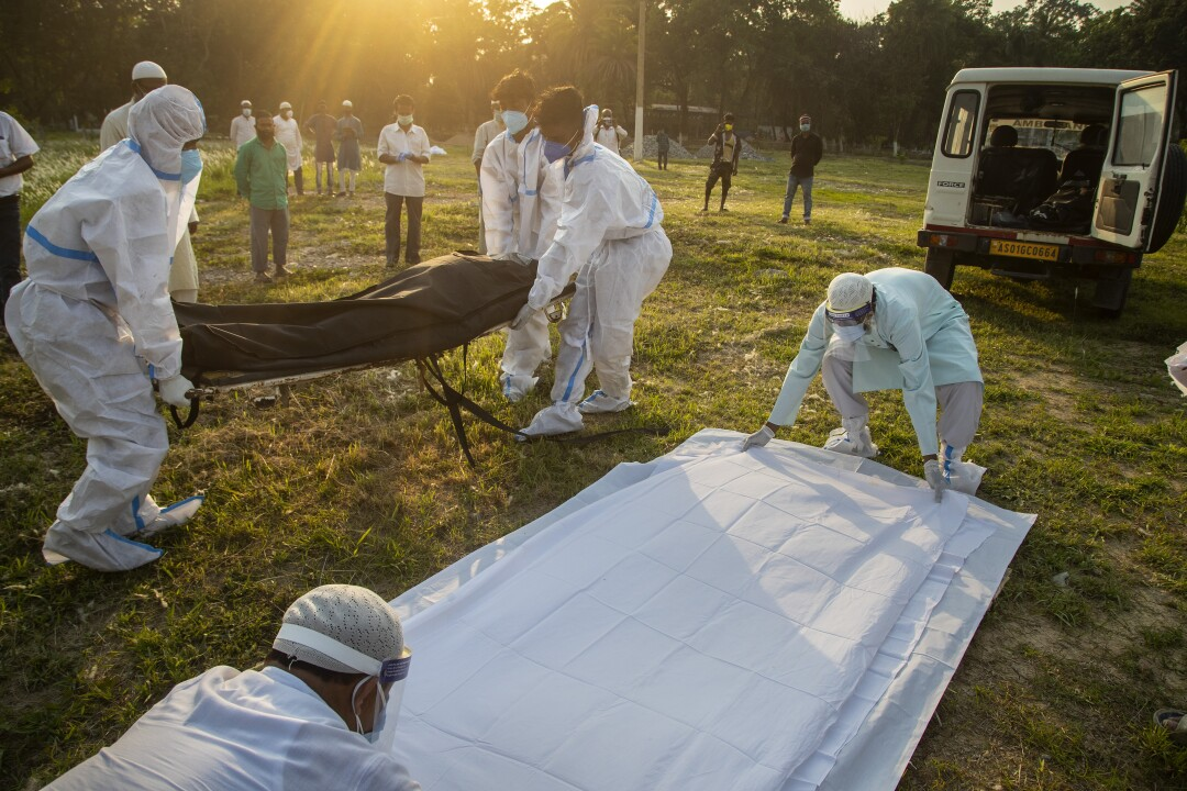 Workers in white protective suits, left, carry a black body bag. Two more workers lay out white sheets on the grass nearby.