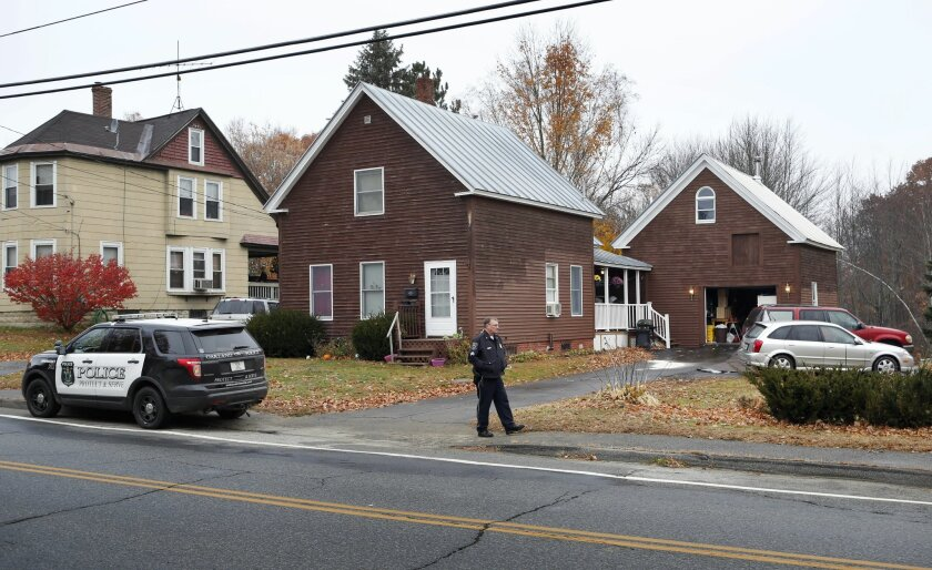 A police officer walks outside a house Thursday, Nov. 5, 2015, where two women and a man were shot to death in Oakland, Maine. Police say the gunman shot himself outside the residence and was found in the driveway.  (AP Photo/Robert F. Bukaty)