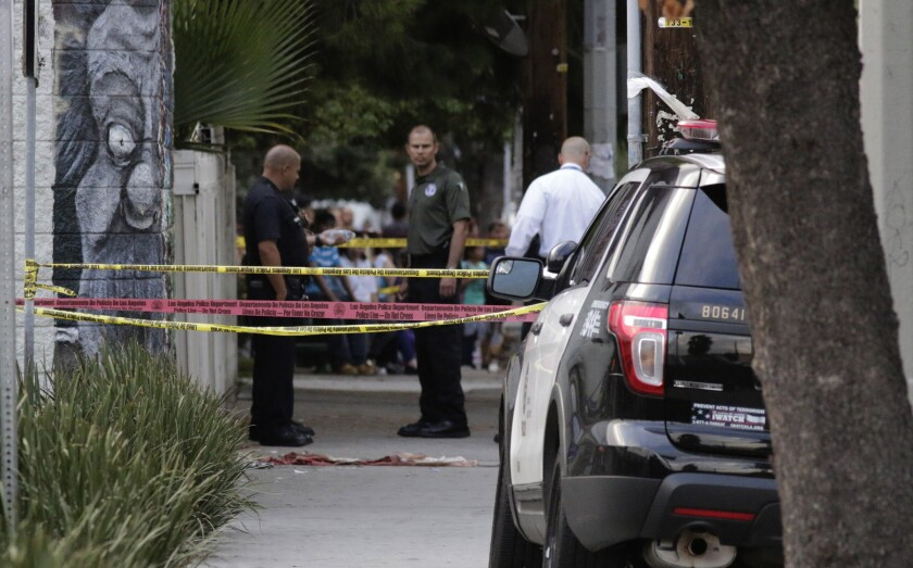 Investigators examine the scene where police fatally shot a man holding a gun Tuesday afternoon in the 14700 block of Parthenia Street in Panorama City.