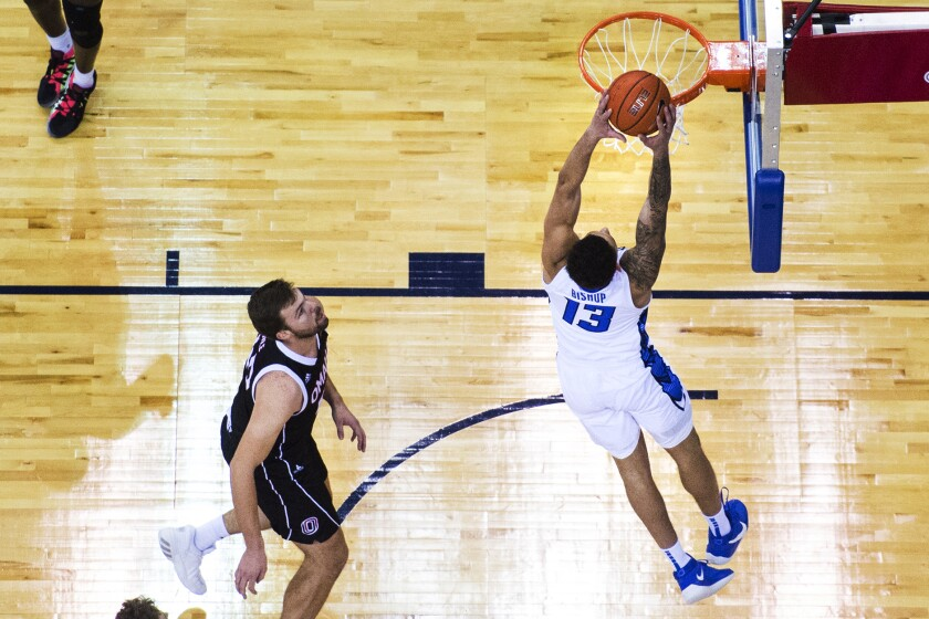 Creighton's Christian Bishop scores against Omaha's Matt Pile during the first half of an NCAA college basketball game in Omaha, Neb., Tuesday, Dec. 1, 2020. (AP Photo/Kayla Wolf)