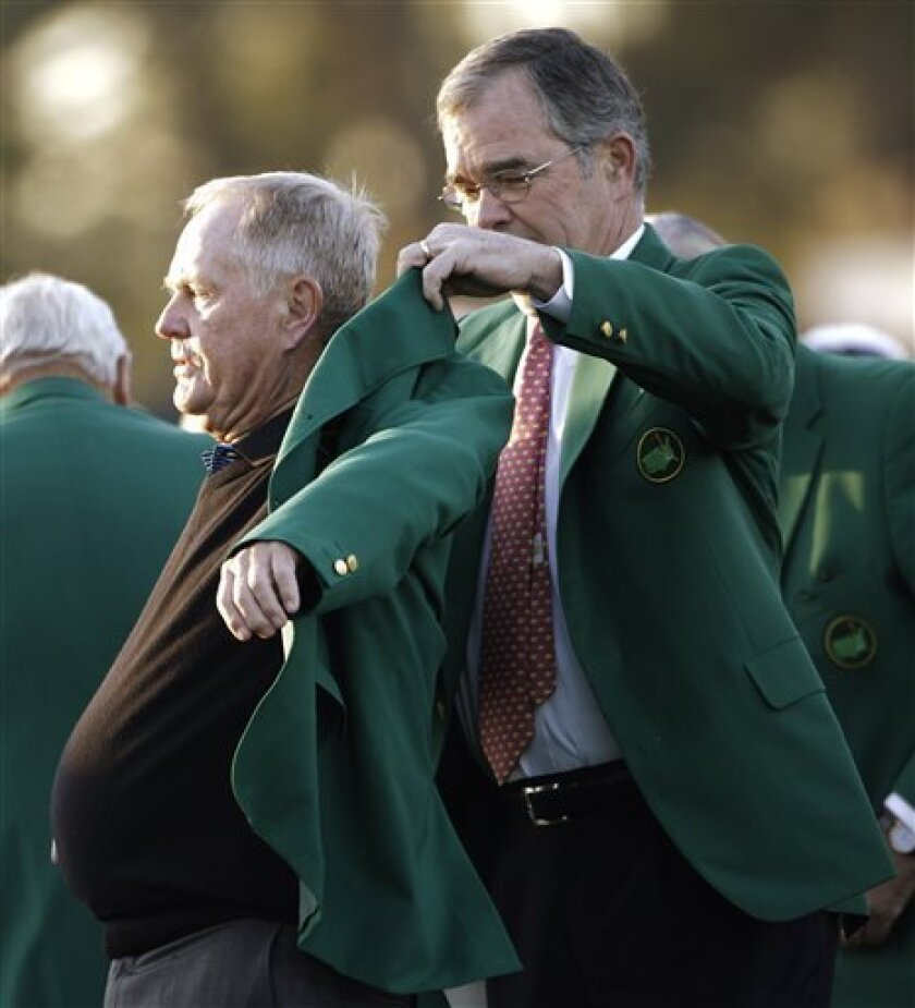 Billy Payne, chairman of Augusta National and the Masters, helps Jack Nicklaus with his green jacket before the first round of the Masters golf tournament Thursday, April 7, 2011, in Augusta, Ga. (AP Photo/David J. Phillip)