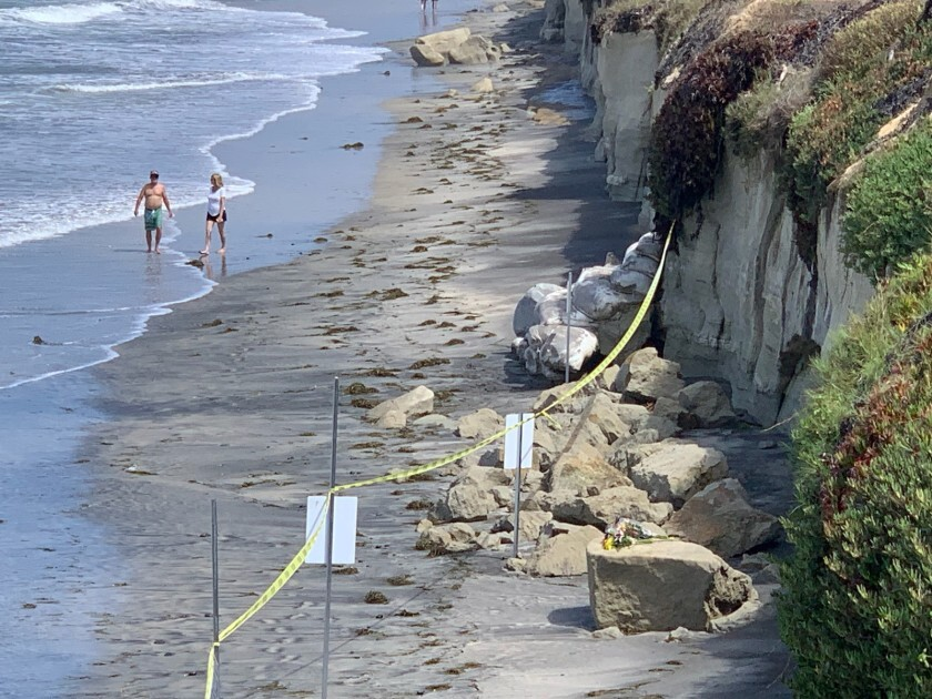 People walk near the site of a deadly bluff collapse in August at Grandview Beach in Encinitas. Three people on the narrow beach died when a large chunk of sandstone slid off the cliff.