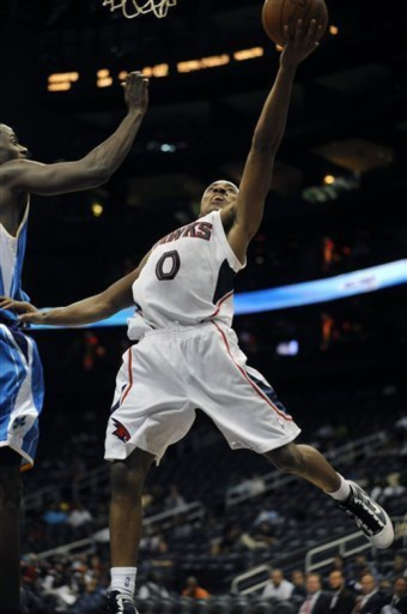 Atlanta Hawks guard Jeff Teague (0) goes up against New Orleans Hornets center Earl Barron, left, during the fourth quarter of an NBA preseason basketball game at Philips Arena, Wednesday, Oct. 7, 2009, in Atlanta. Teague led the Hawks with 19 points for the night as the they won 108-102. (AP Photo/Gregory Smith)