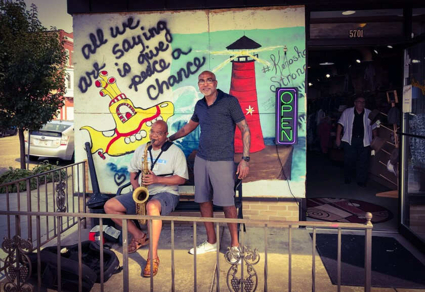 Shad DeLacy stands next to a seated saxophone player in front of a yellow submarine mural on a storefront