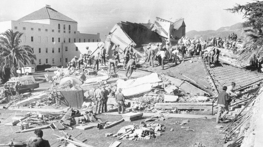 Workers swarm the VA hospital in Sylmar that was destroyed in the 1971 earthquake centered nearby.