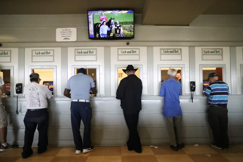People stand at betting windows.